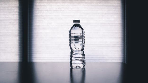 Clear Disposable Bottle on Black Surface. image used in tip to stop buying bottled water in my Small Ways to Save Money