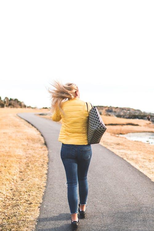 Woman Wears Yellow Bubble Jacket Walk Through Gray Asphalt Way