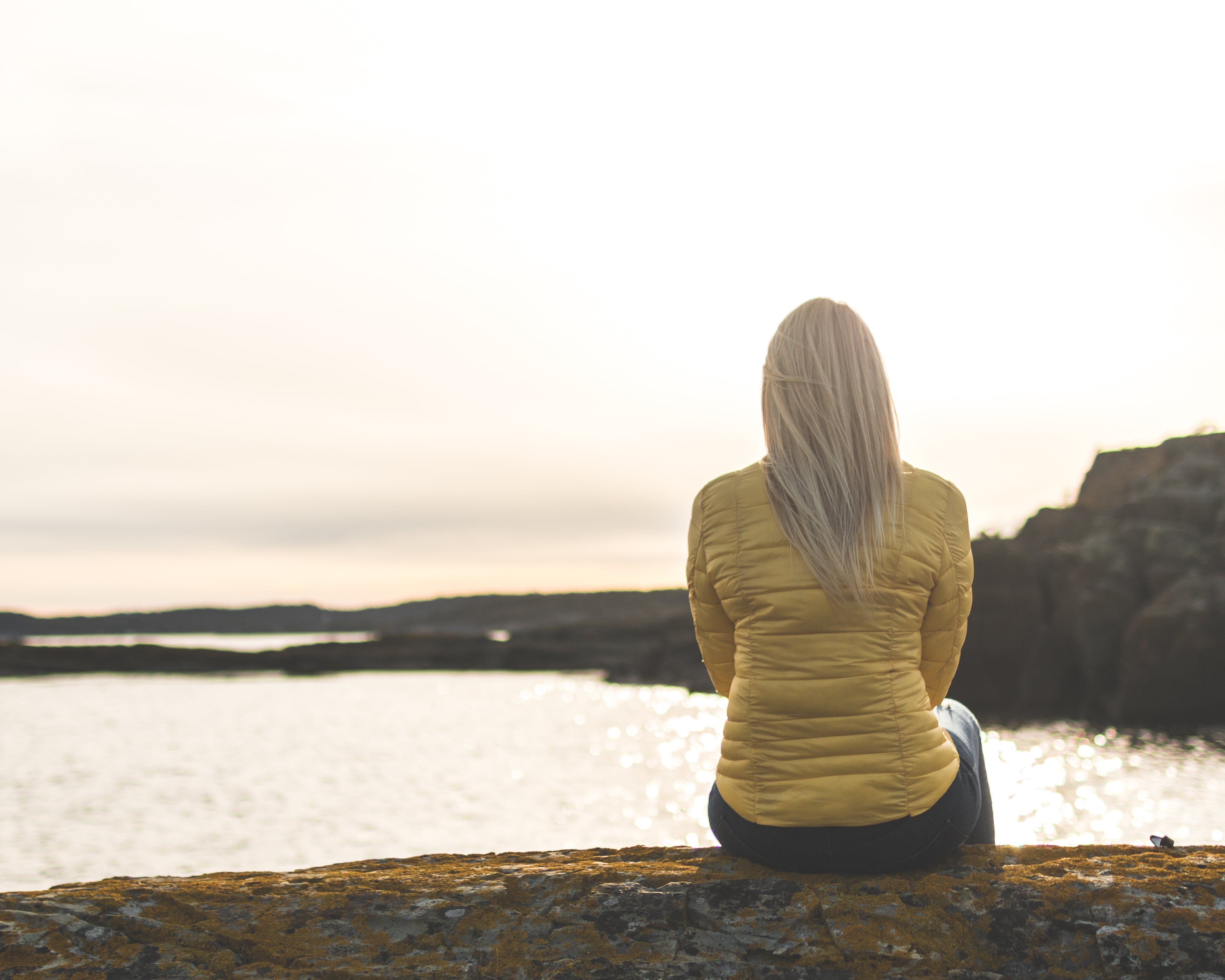 Woman Wearing Yellow Bubble Jacket Sitting in Front of Sea