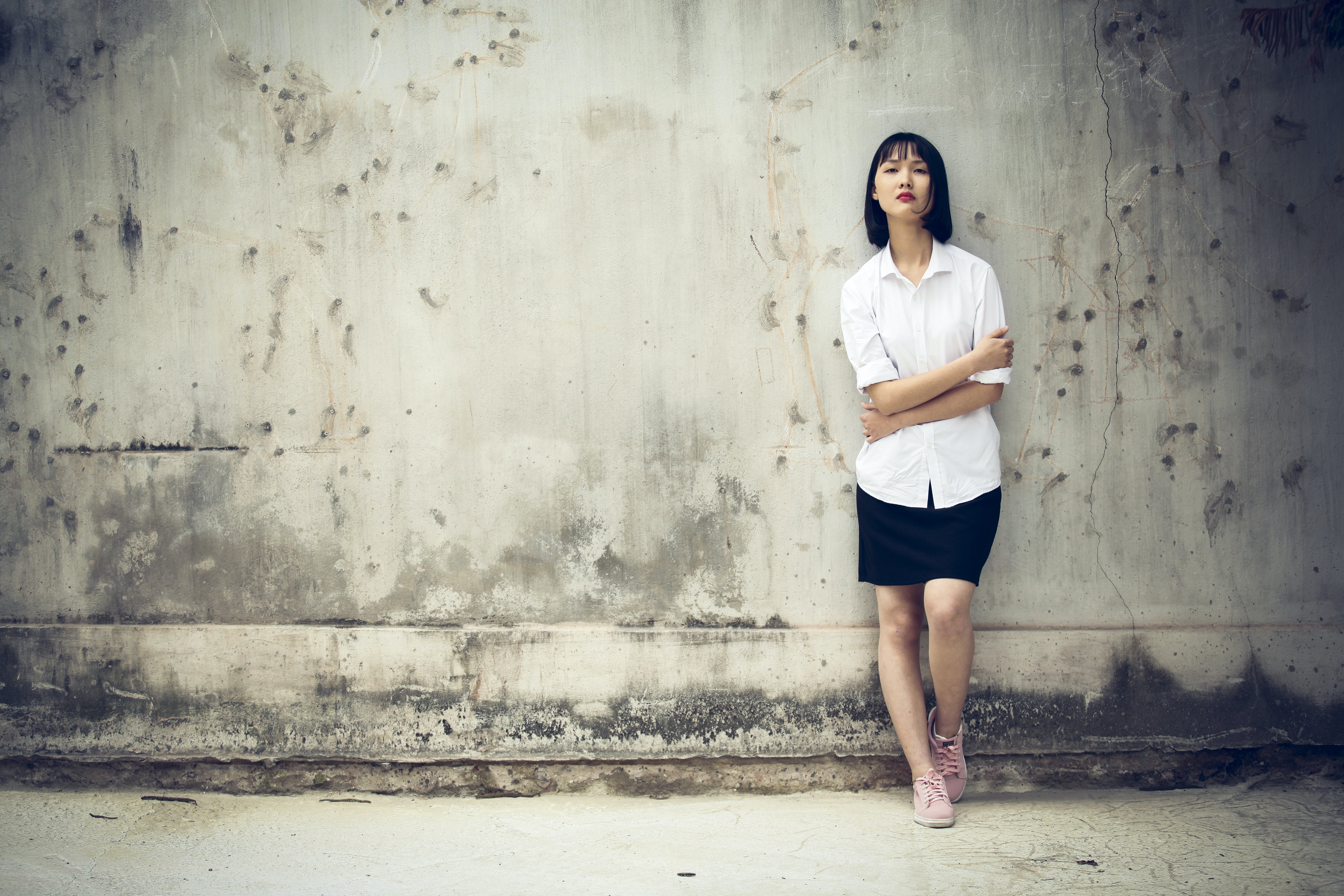Woman Standing Next to a Wall