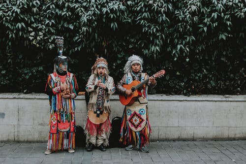 Three Men in Traditional Native American Clothes Playing Guitar on Side of Road