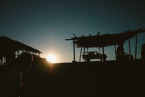 Silhouette of Pickup Truck Near Hut