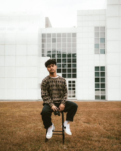Portrait of Young Man with Camera Sitting in Front of Building