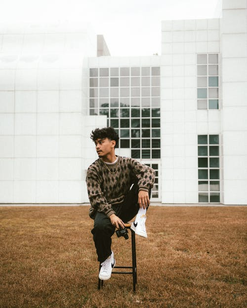 Young Man with Camera Sitting in Front of Building