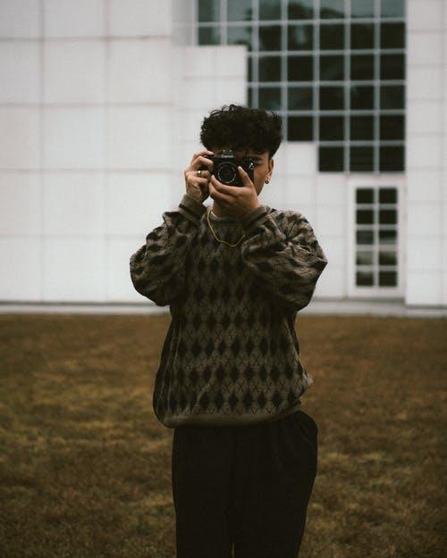 Young Man with Camera Standing in Front of Building