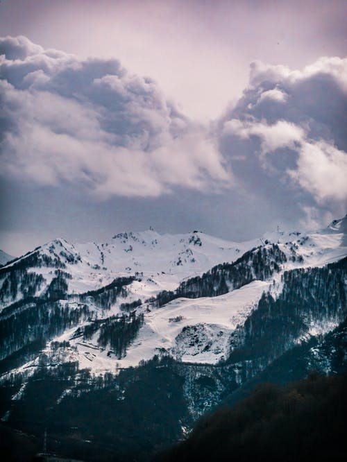 Photography of Snow Capped Mountain Under Cloudy Sky