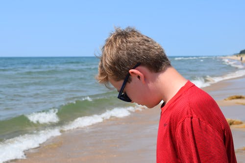 Photo of Boy Wearing Red Shirt and Sunglasses On Seashore