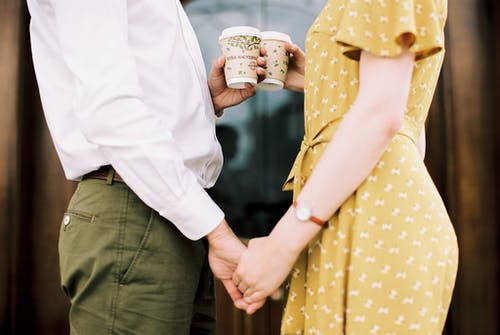 Close-up of Couple with Disposable Coffee Cups Holding Hands