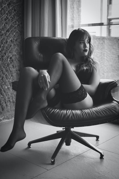 Black and White Picture of Woman Sitting on Armchair