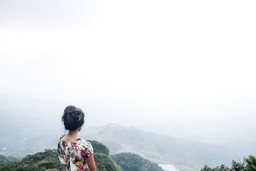 Woman Wearing Multicolored Floral Top Standing Near Mountain Under White Sky