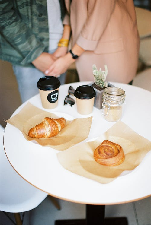 Couple Holding Hands at Table with Buns and Coffee