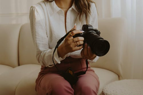 Unrecognized Woman Sitting on Sofa Holding Camera with Telephoto Lens