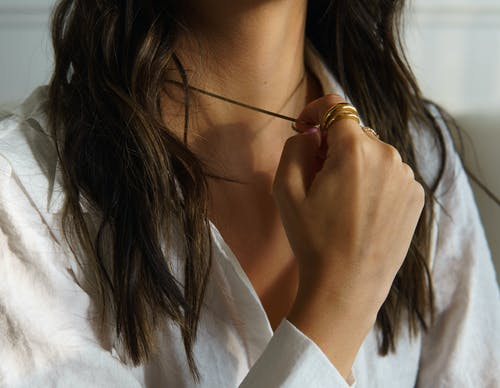 Unrecognized Young Womans Hand Pulling Pendant on Her Neck