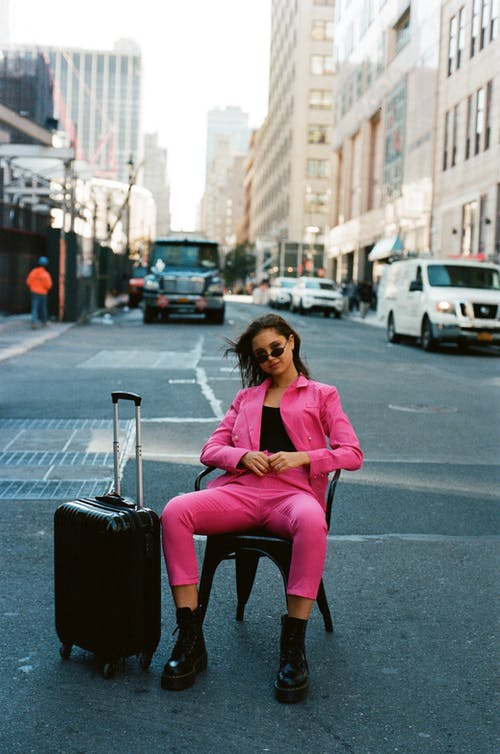 Woman in Pink Suit Sitting on Chair on Street