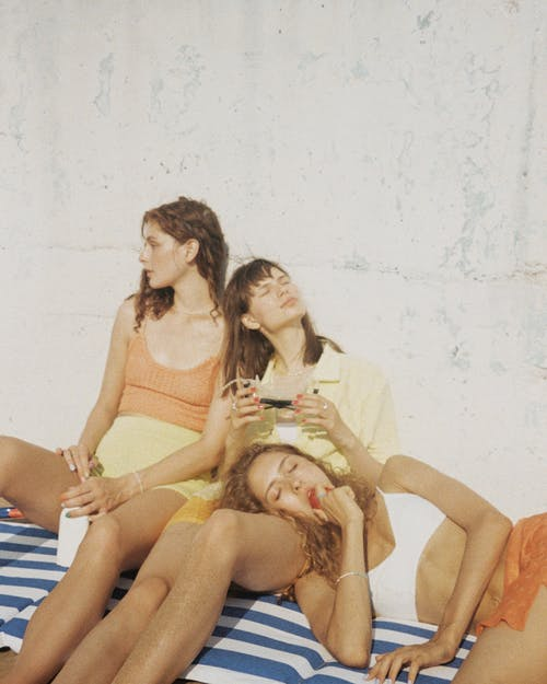 3 Women Sitting on Blue and White Striped Sofa