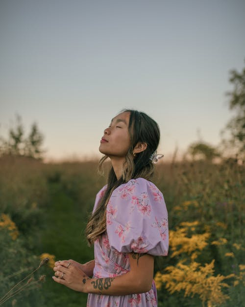 Woman Standing in Field at Sunset