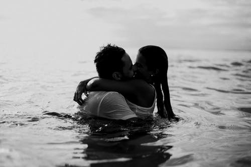 Man and Woman Kissing Together on Body of Water