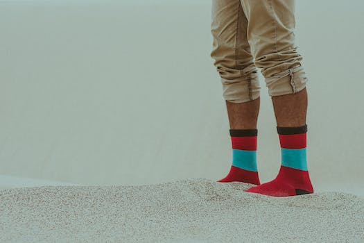 Person Wearing Red Socks Standing on Sand