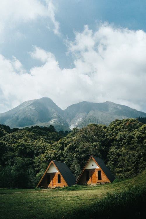 Brown Wooden House on Green Mountain Under White Clouds