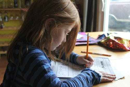 Girl Drawing On Brown Wooden Table