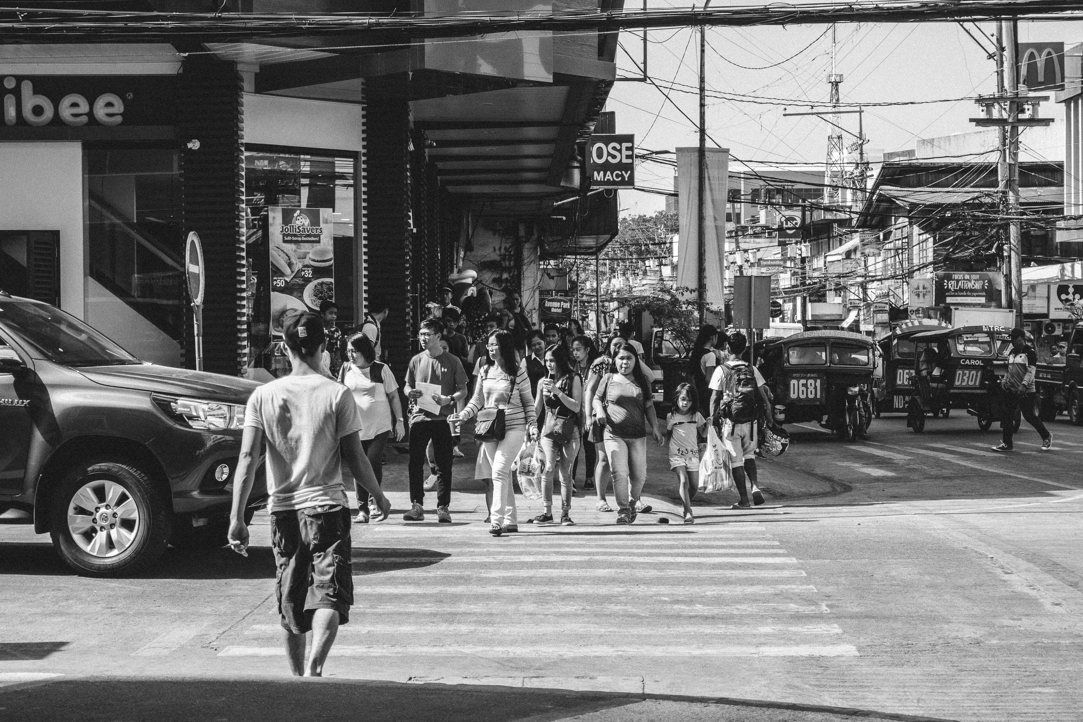 Monochrome Photography of People Crossing The Road