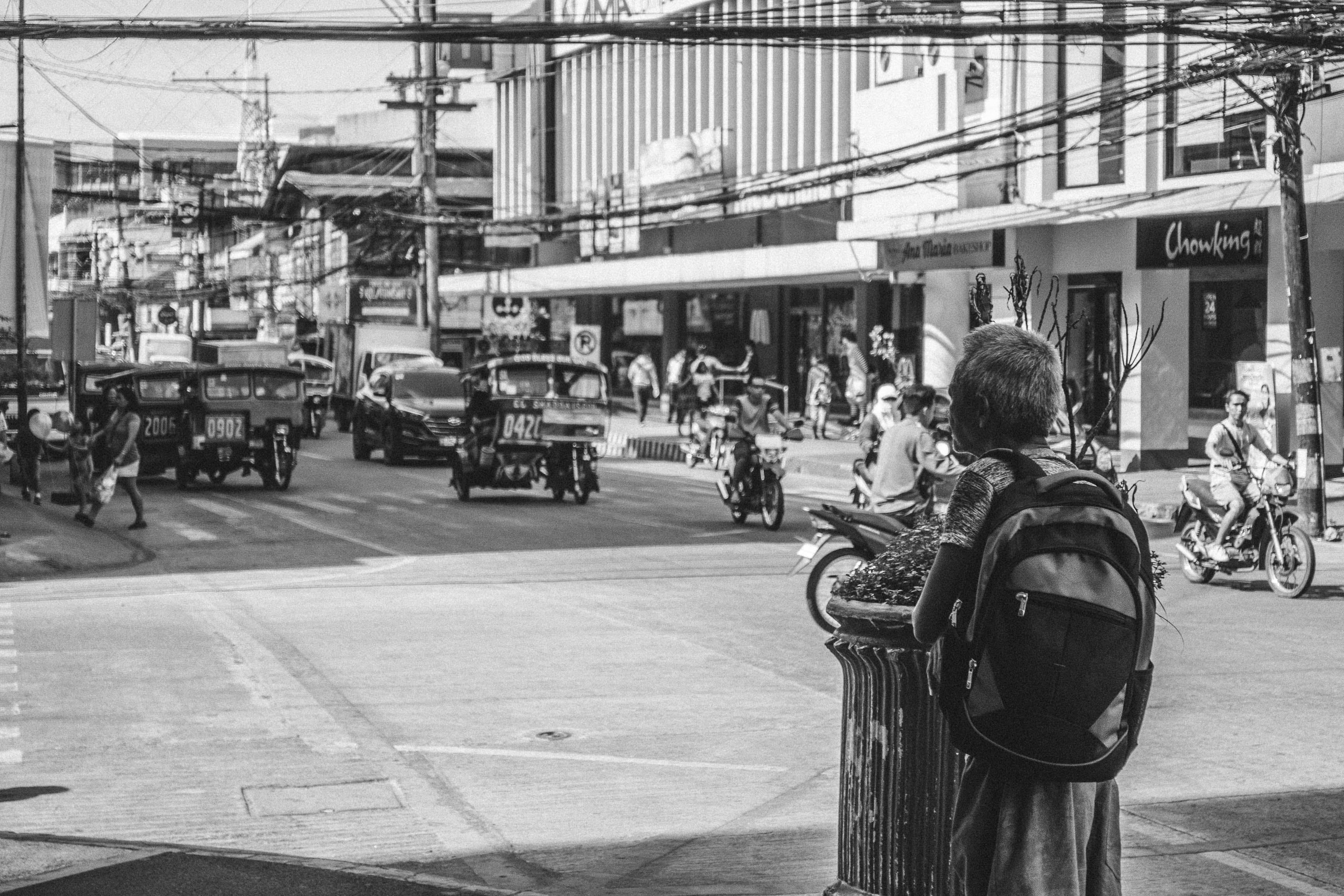 Person Wearing a Backpack in the Middle of the Street in Grayscale Photo