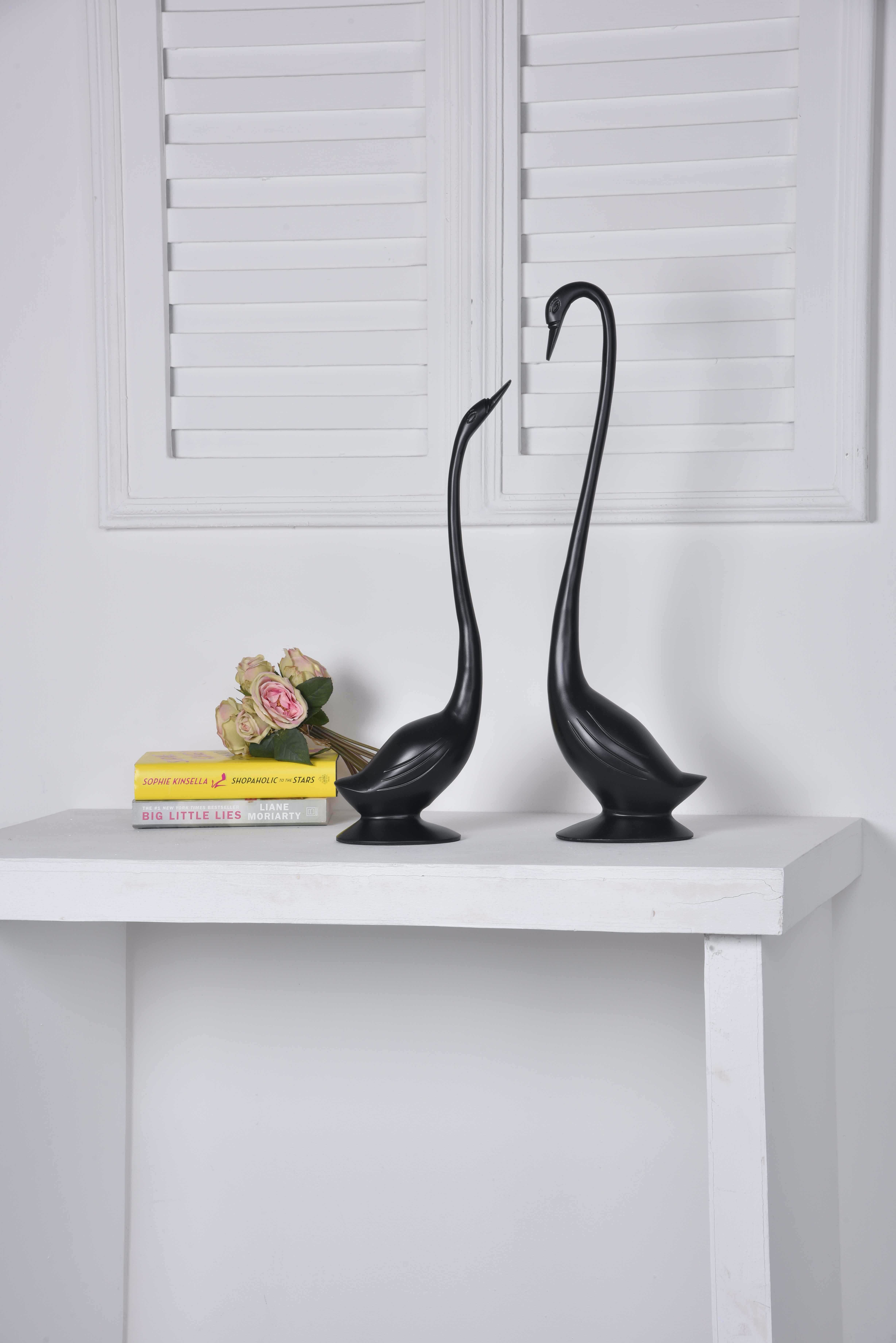 Two Black Geese Figurines on White Console Table
