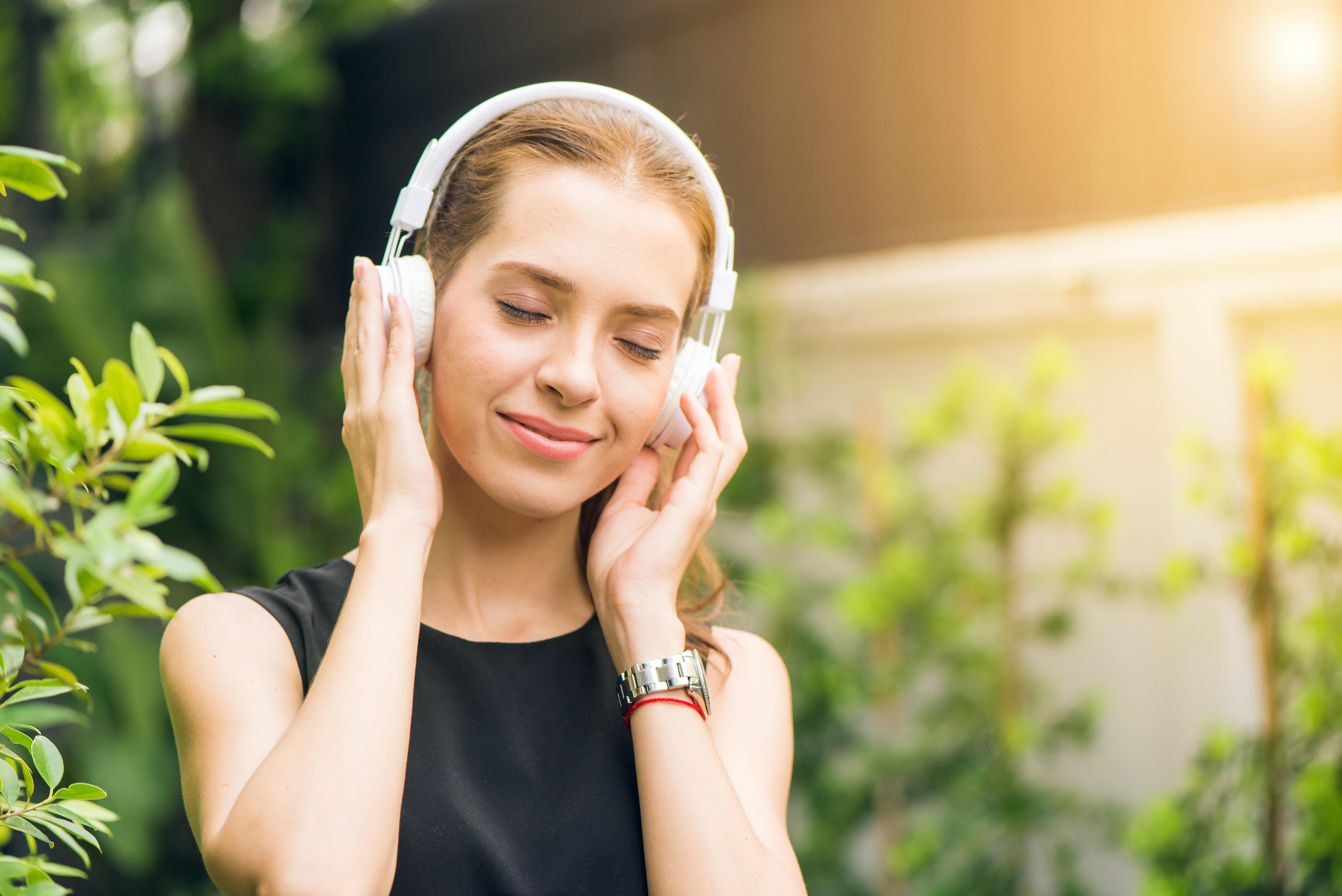 a9f0f0b8b50 Woman Wearing Black Sleeveless Dress Holding White Headphone at ...