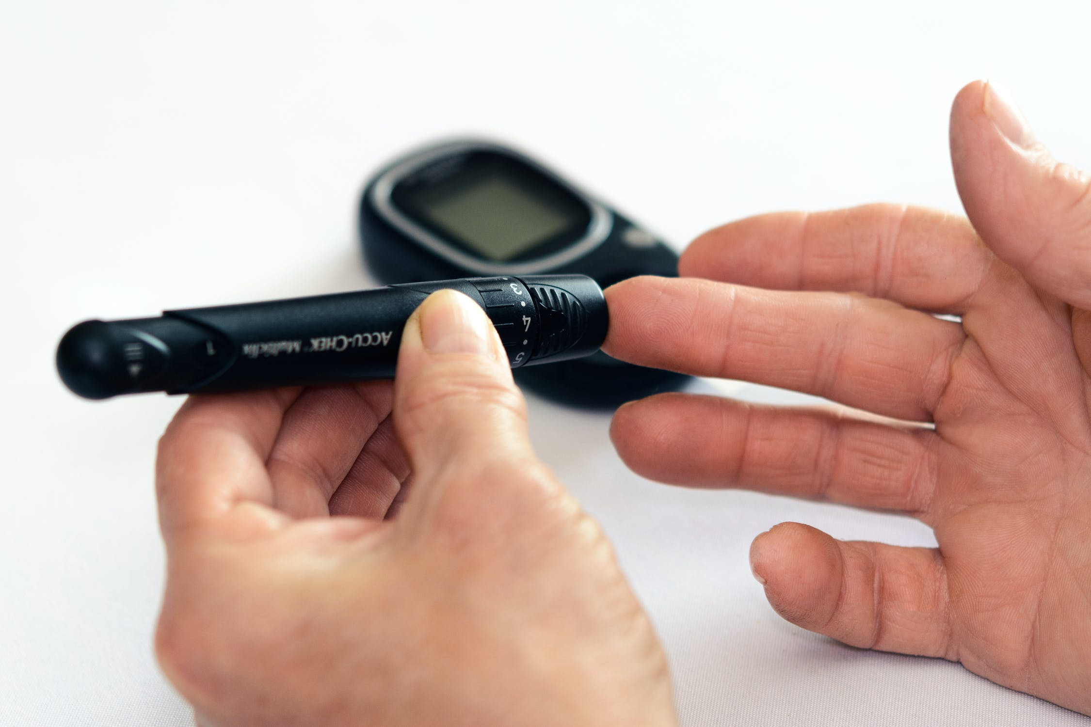 A person's hands checking their blood sugar levels. Photo by pexels user PhotoMIX Company. Photo used courtesy of pexels
