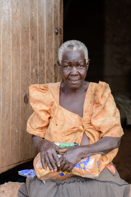Photo of a Woman Sitting Near a Wooden Door