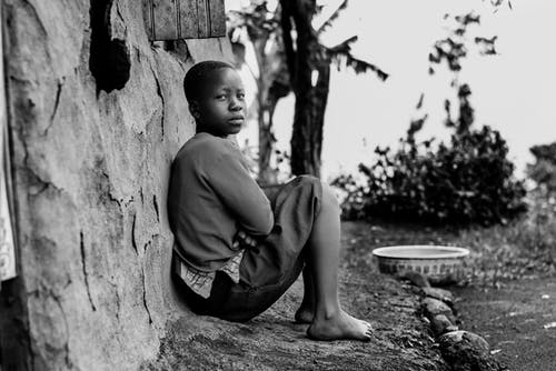 Greyscale Photography of Boy Sitting Behind Wall
