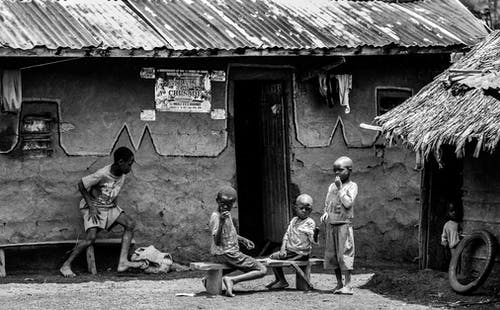 Greyscale Photo of Children in Front of a House at Daytime