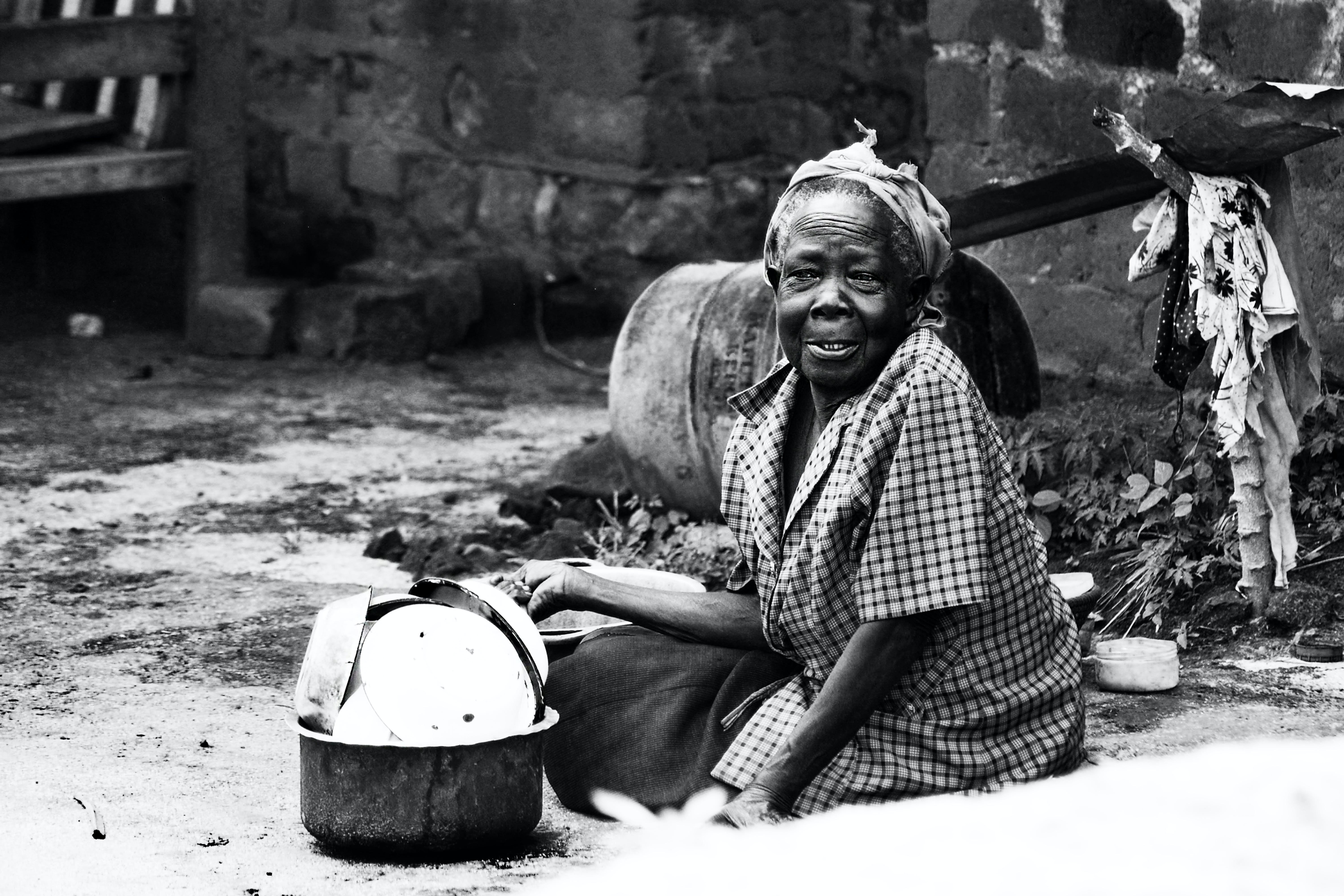 Woman Sitting on Soil Beside Cooking Pot