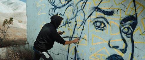 Woman in Black Hoodie Painting on Wall