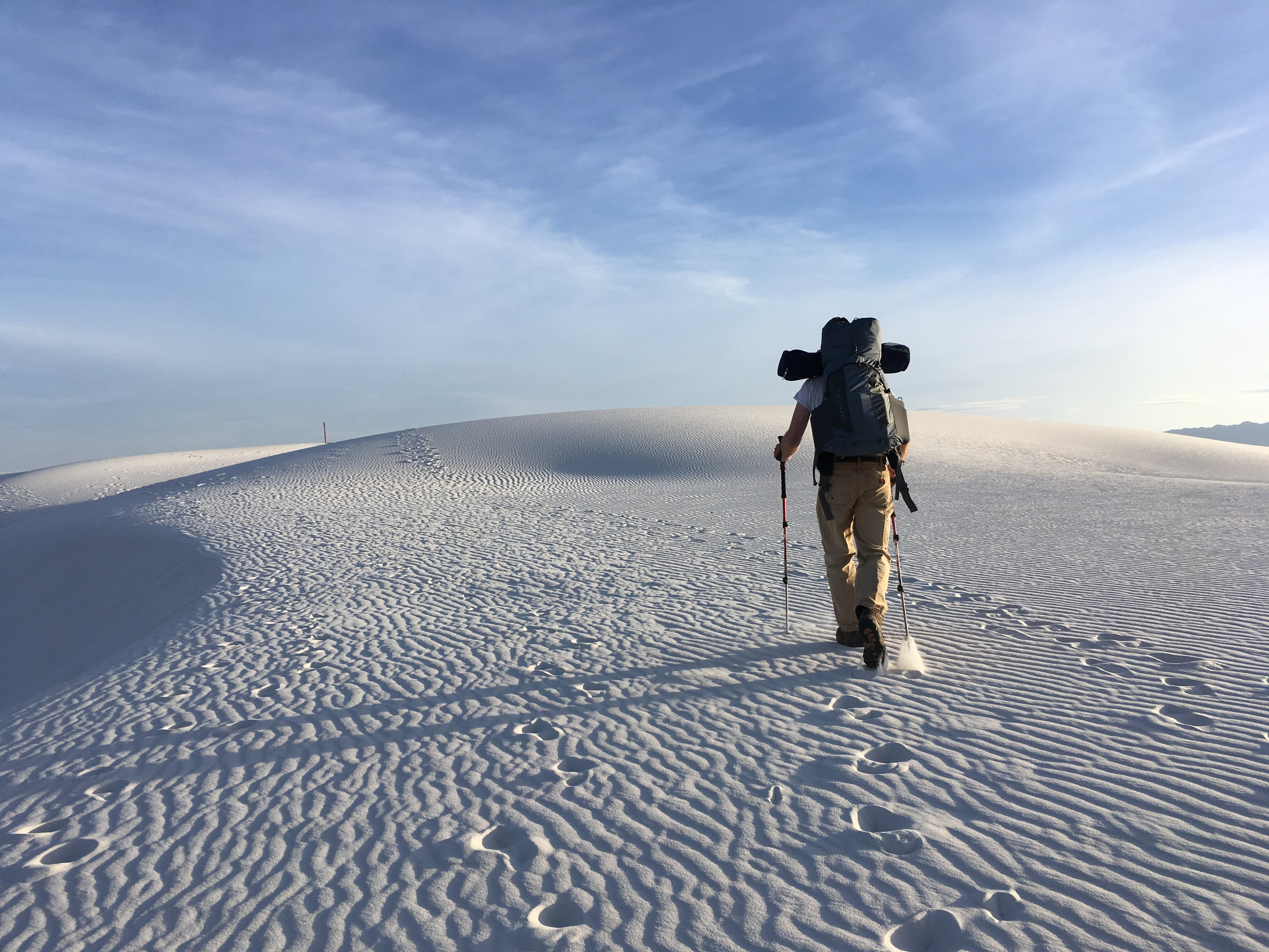 Photo of Man Holding Hiking Poles on Snow Field