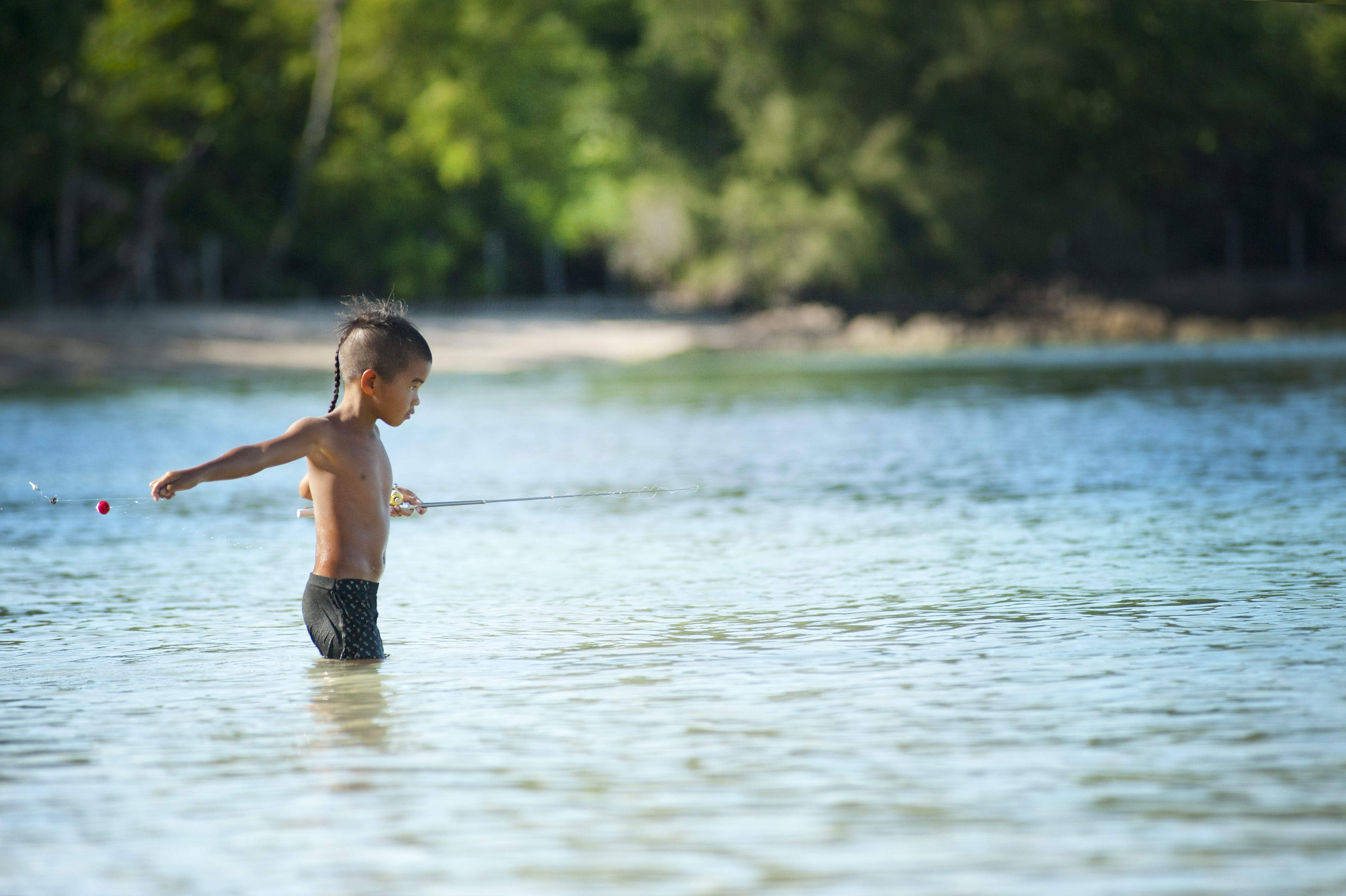 Topless Boy Wearing Black Shorts Standing on Bodies of Water