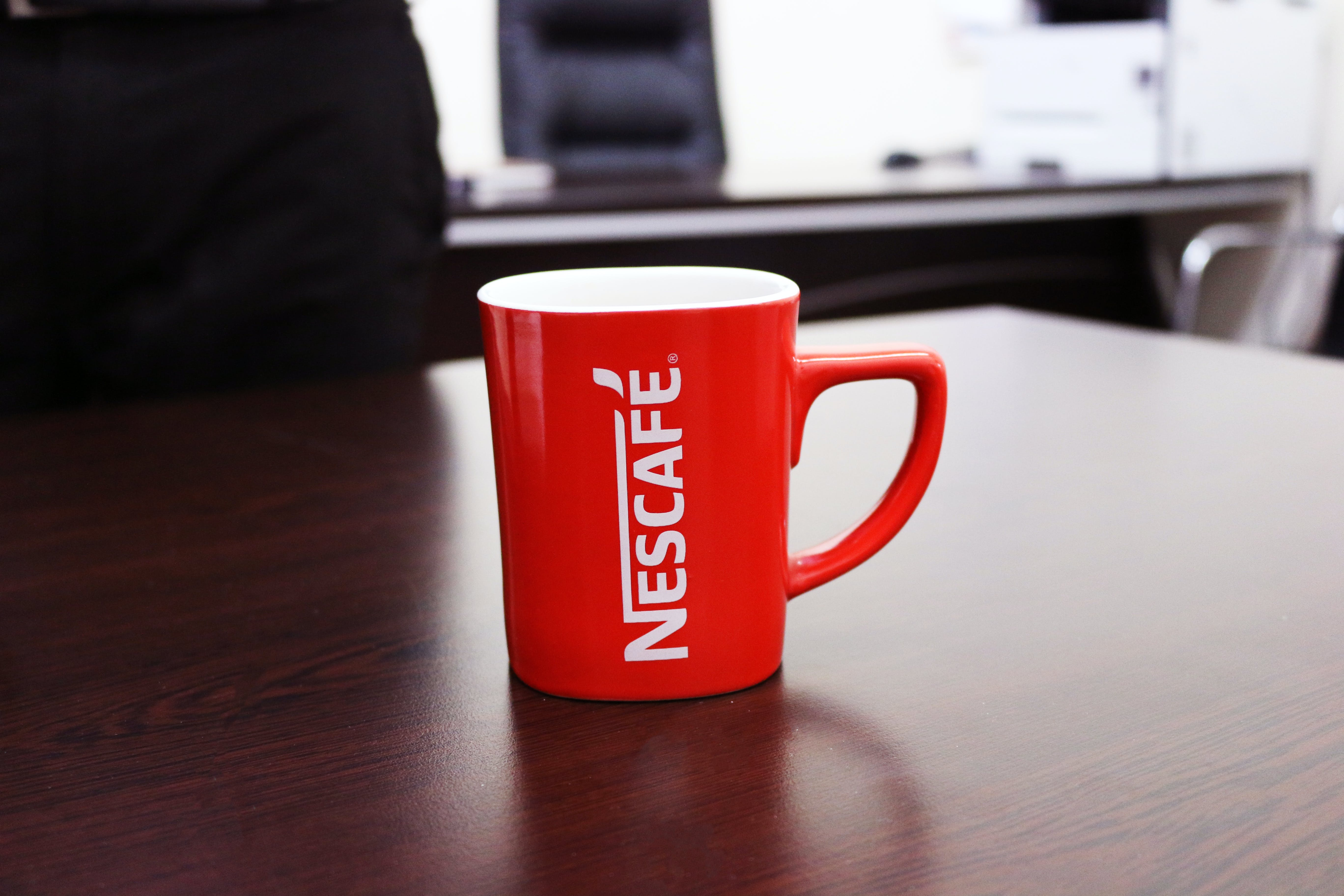 Red and White Nescafe-printed Mug on Brown Wooden Table