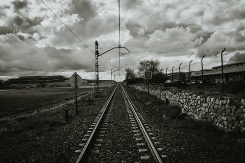 Grayscale Photograph of Train Rail