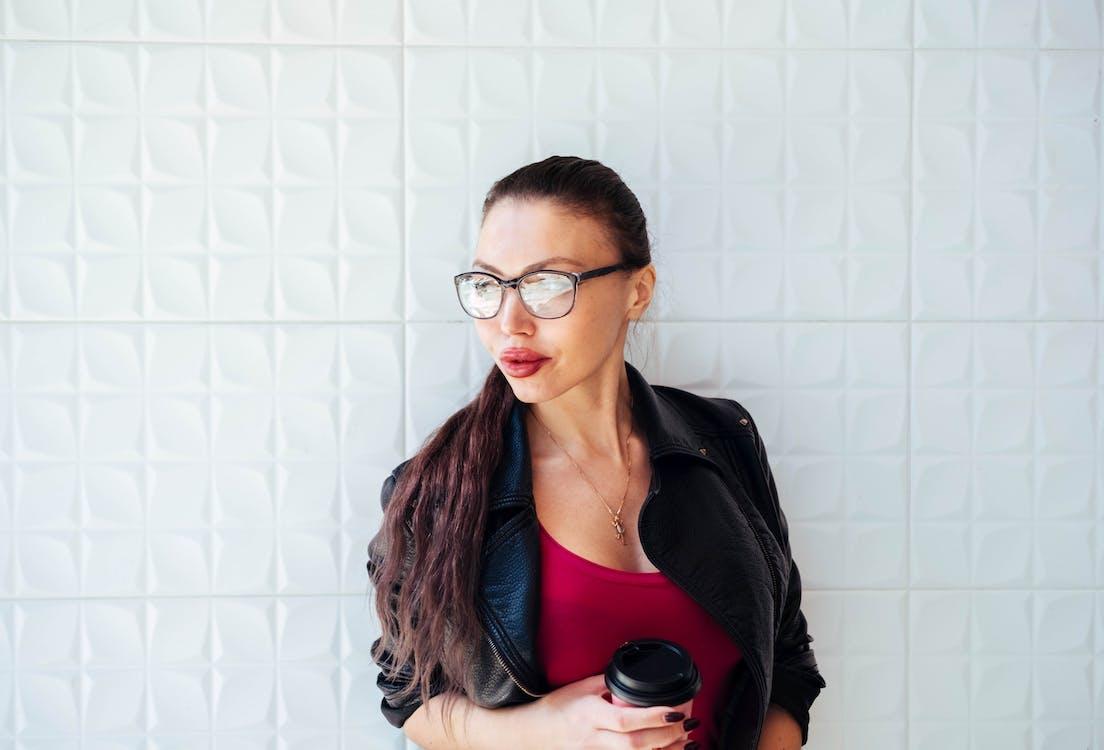 Woman in Black Leather Jacket Wearing Eyeglasses Holding Coffee Cup