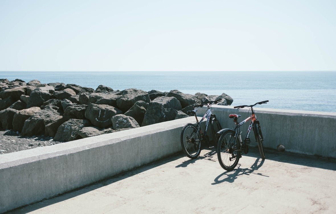 Two Bicycles Behind Gray Concrete Wall