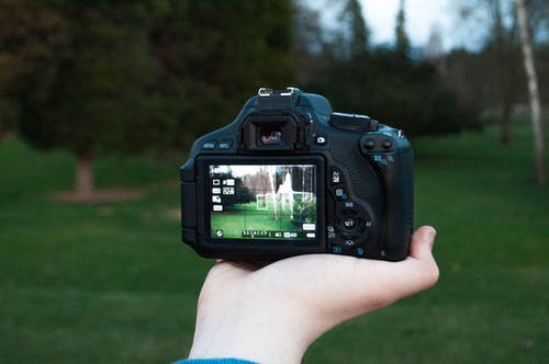 Shallow Focus Photography of Black Dslr Camera on Person's Right Hand