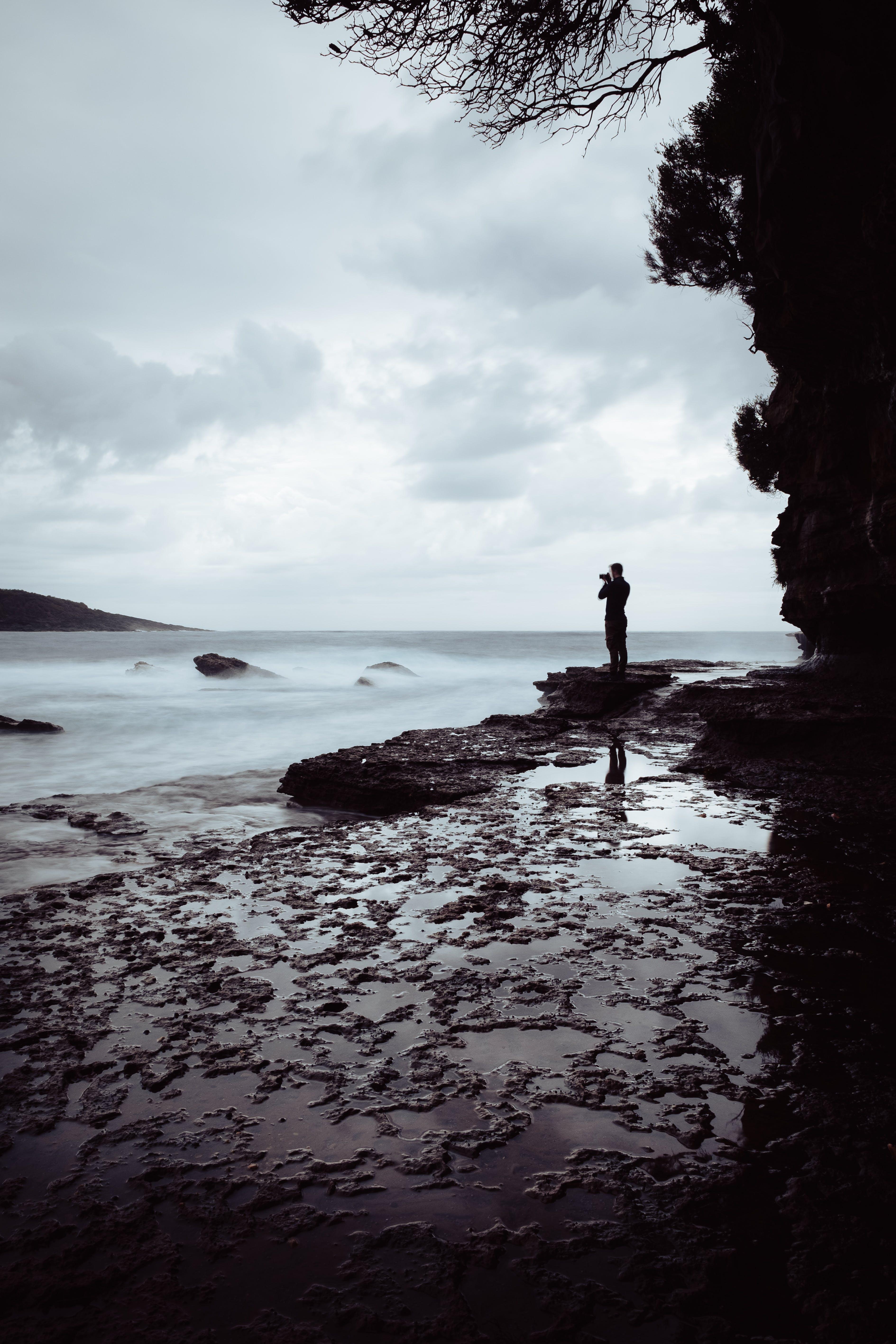 Man Standing on Rock Near Ocean