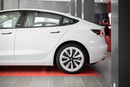 White Sedan Parked on Red Floor Tiles