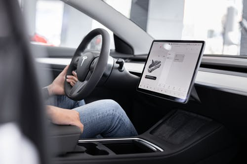 Person in Blue Denim Jeans Sitting on Driver Seat