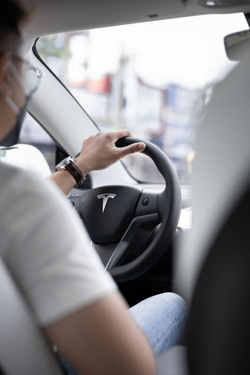 Person in White Long Sleeve Shirt Driving Car