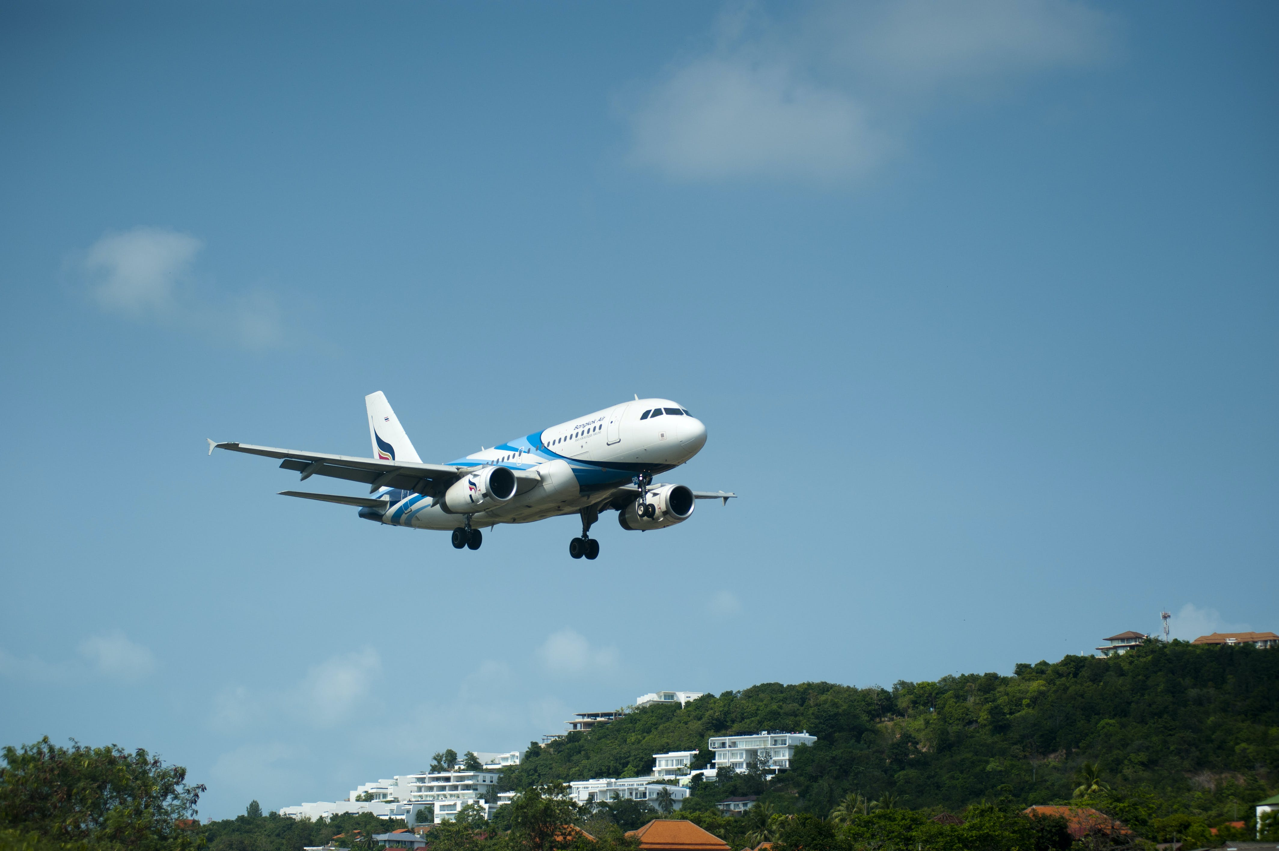 White and Blue Passenger Plane Passing Above Green Tree Covered Hill