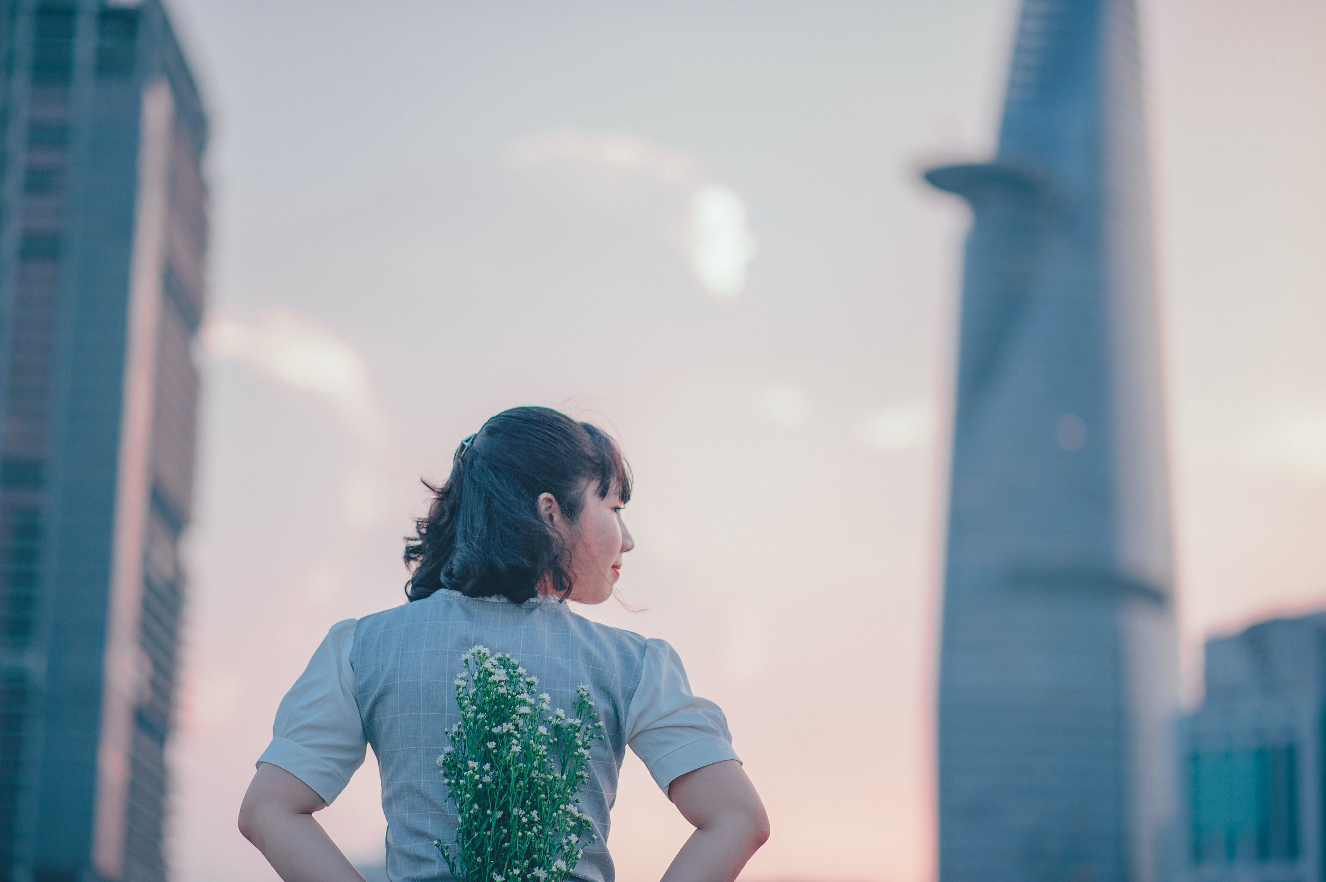 photo of Woman in Gray Top Holding Flowers on Her Back