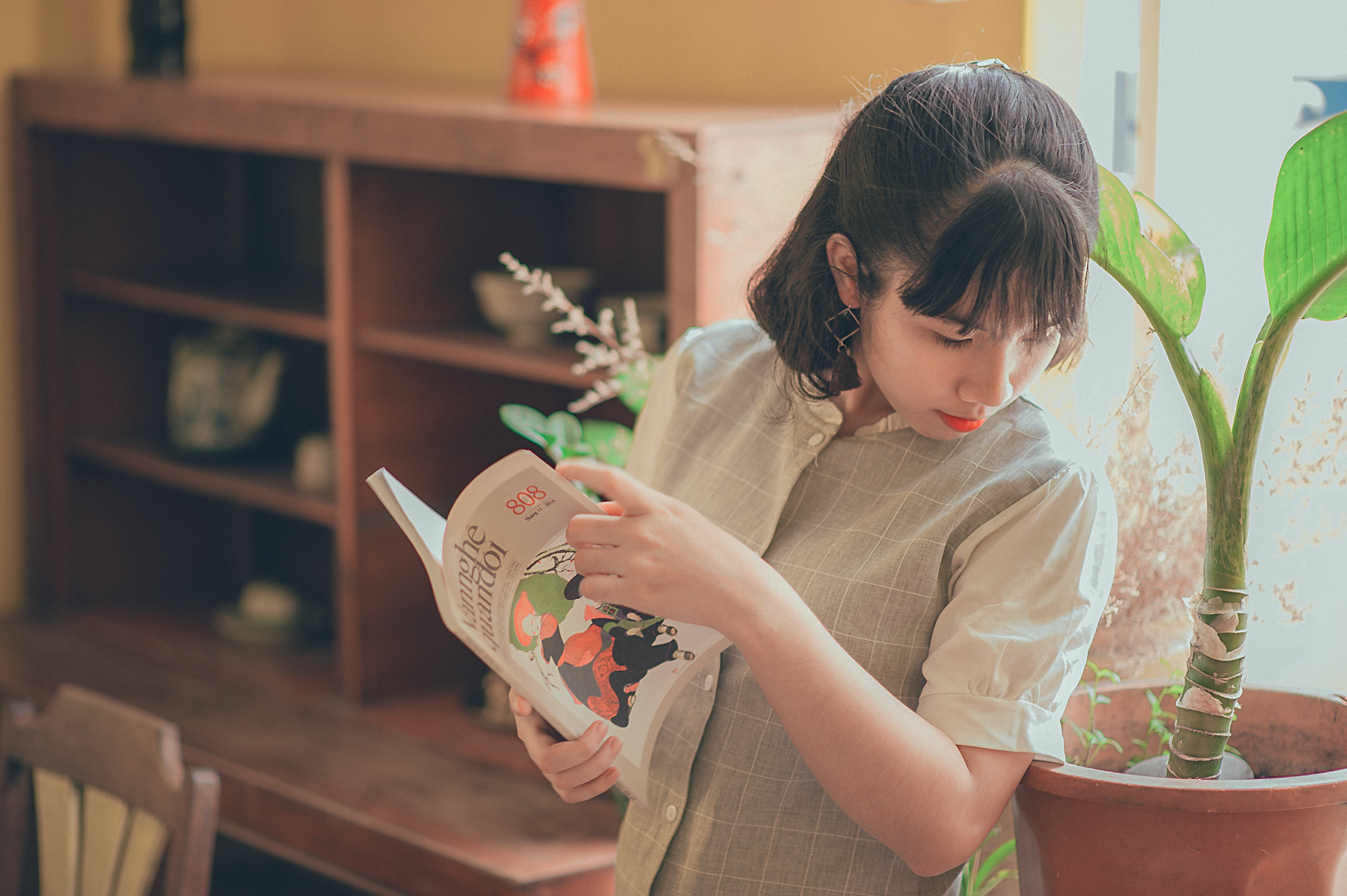 Woman in Grey Button-up Short-sleeved Top Holding Book