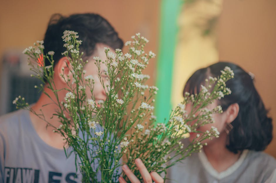 Photo of Man and Woman Behind the Flowers