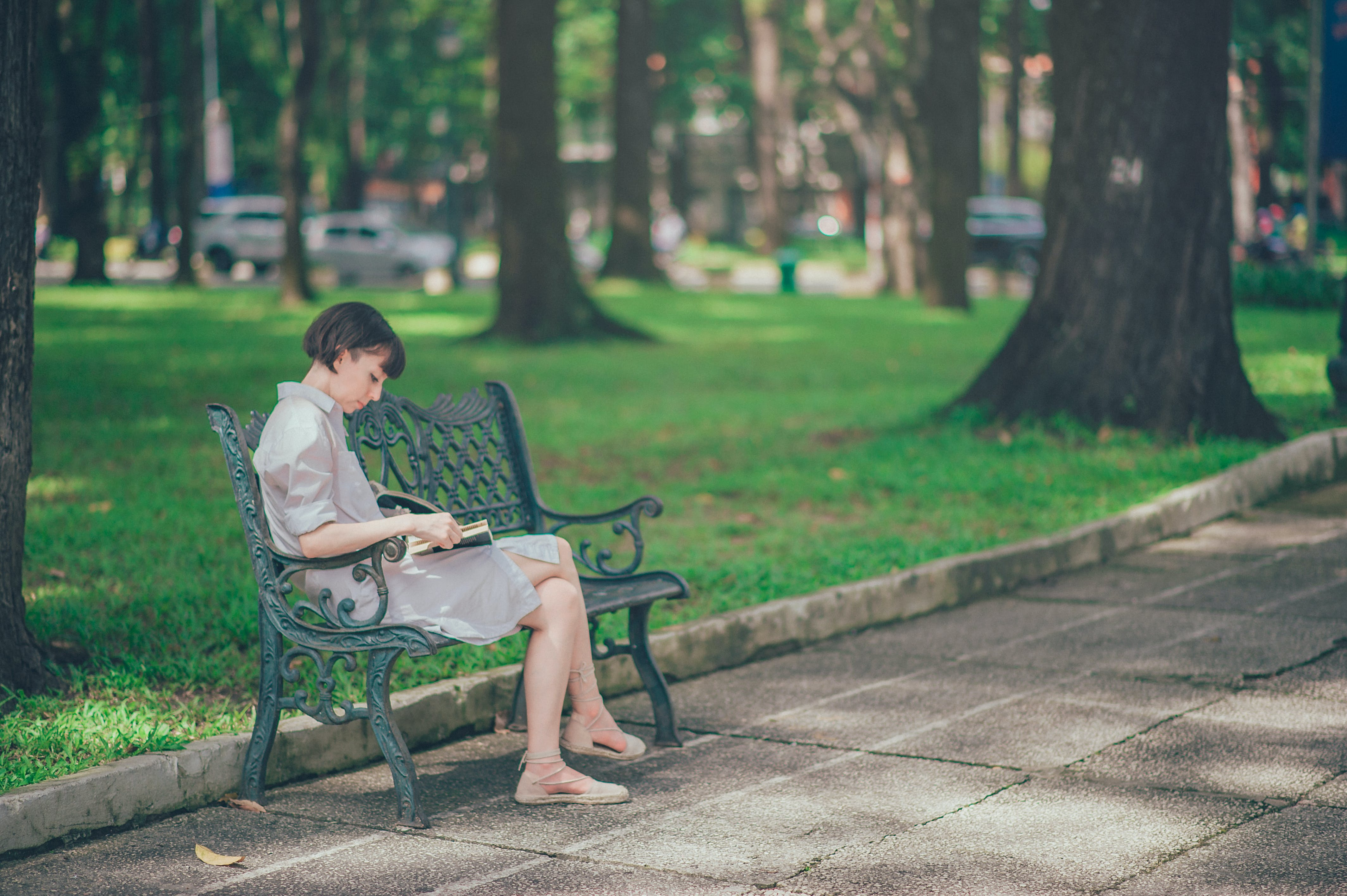 Photo of Woman Wearing Gray Dress Sitting on Bench